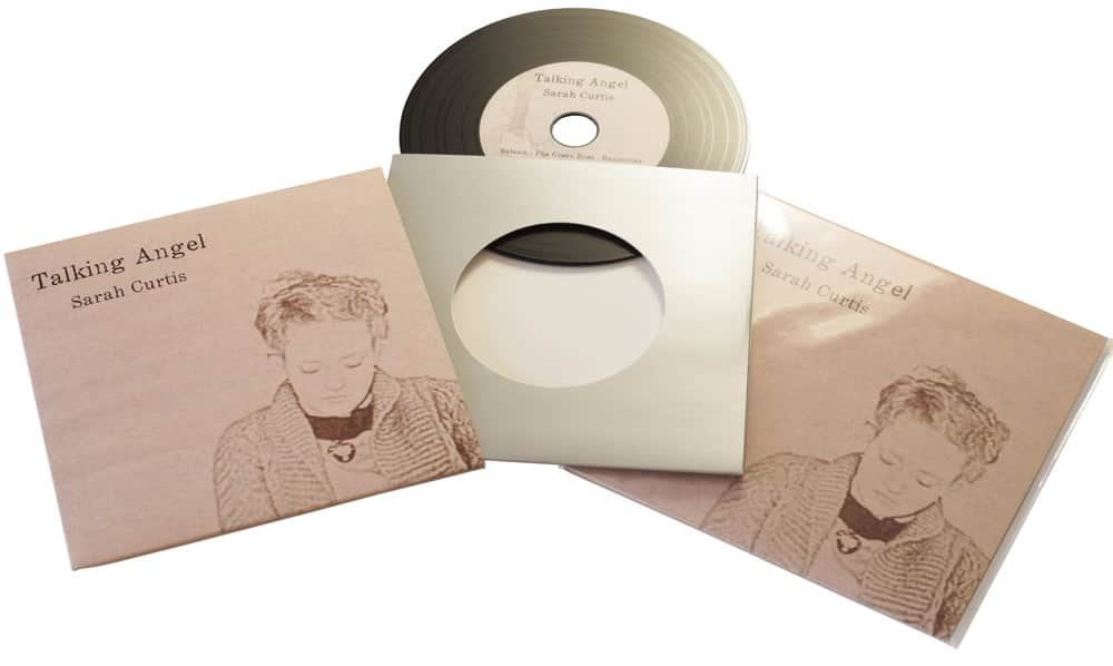 Vinyl CDs in plain silver card wallets with a larger outer printed wallet and finished with cellophane wrapping