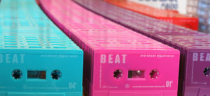 Pre-printed turquoise, hot pink, blackberry purple and red cassettes awaiting recording