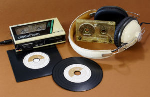 A set of gold glitter cassettes with white on-body printing and black vinyl CDs with a gold print and supplied in plain black record-style wallets
