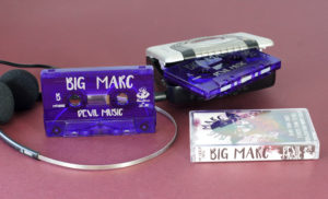 Transparent purple cassette shells with a silver on-body print in clear cases with full colour J-cards
