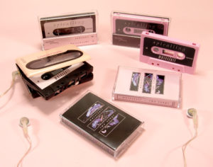 A set of black and baby pink cassettes with J-cards and an additional fold-out panel