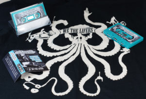 A set of turquoise cassettes in clear cases with J-cards, pictured with a band t-shirt