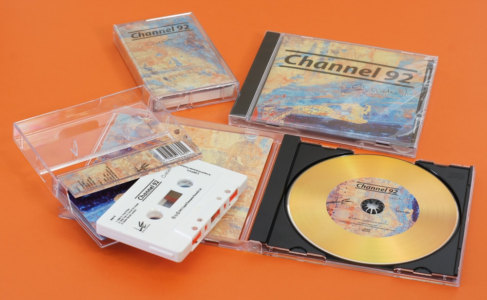 A set of white cassettes with on-body printing and gold vinyl CDs in matching jewel cases, all cellophane wrapped