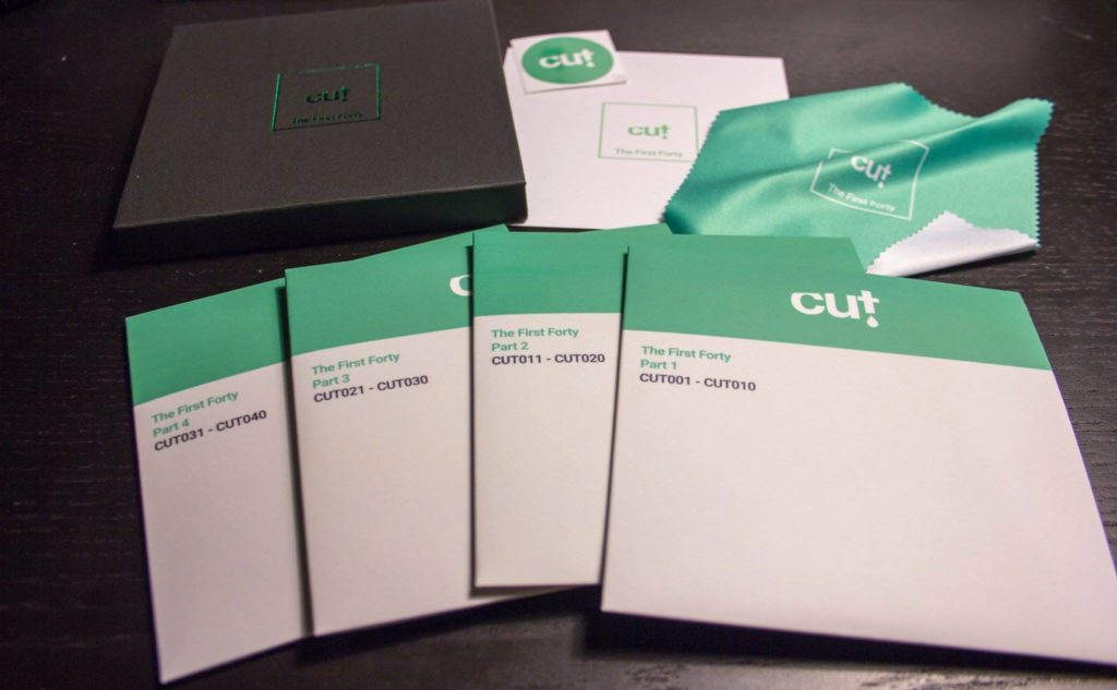 Box set of four premium vinyl CDs in a black matchbox style case with green foil printing
