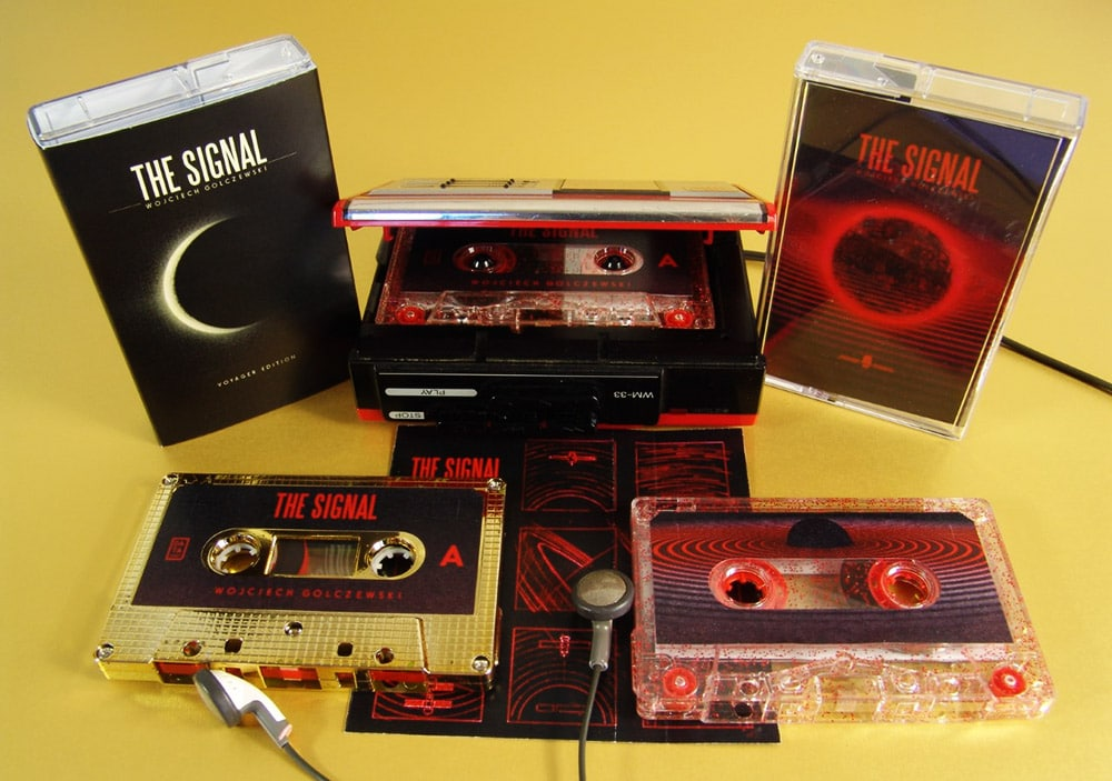 Metallic gold and red glitter cassettes with sticker printing and in cases, with the metallic gold also having outer O-cards