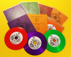 Red, green, orange and purple vinyl CDs in clear wallets with metallic card inserts