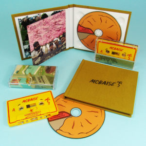 Yellow cassette with full coverage UV LED printing and CDs in hardback linen covered digipaks also with a UV LED cover print