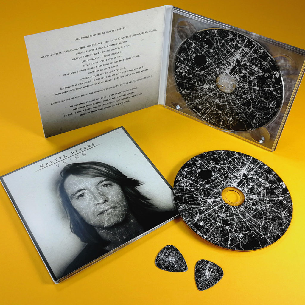 CDs with on-body UV LED printing in four page CD digipaks, with matching printed guitar picks