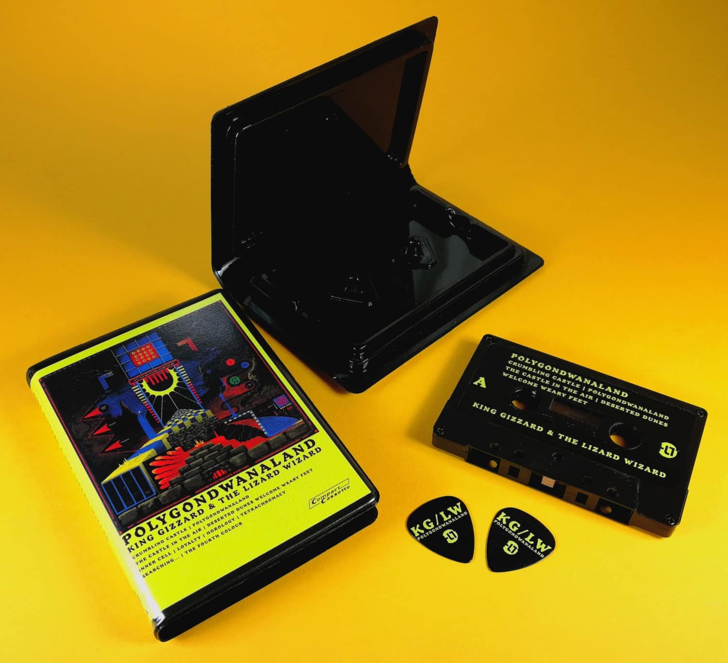 Black cassettes with yellow UV LED printing, supplied in rave cases with printed inserts and matching black guitar picks with yellow UV LED printing