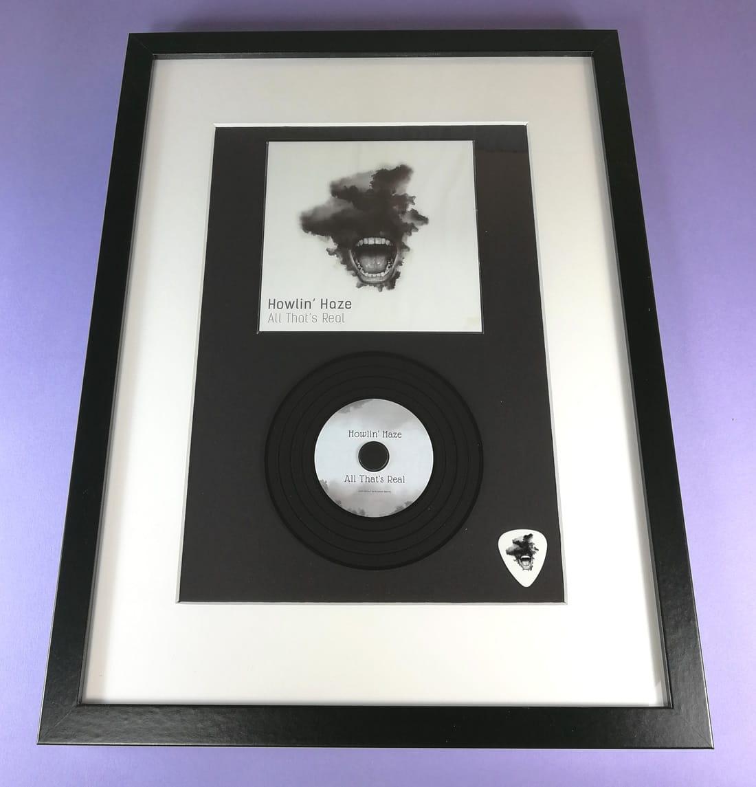 Black presentation frames with vinyl CD and custom guitar pick