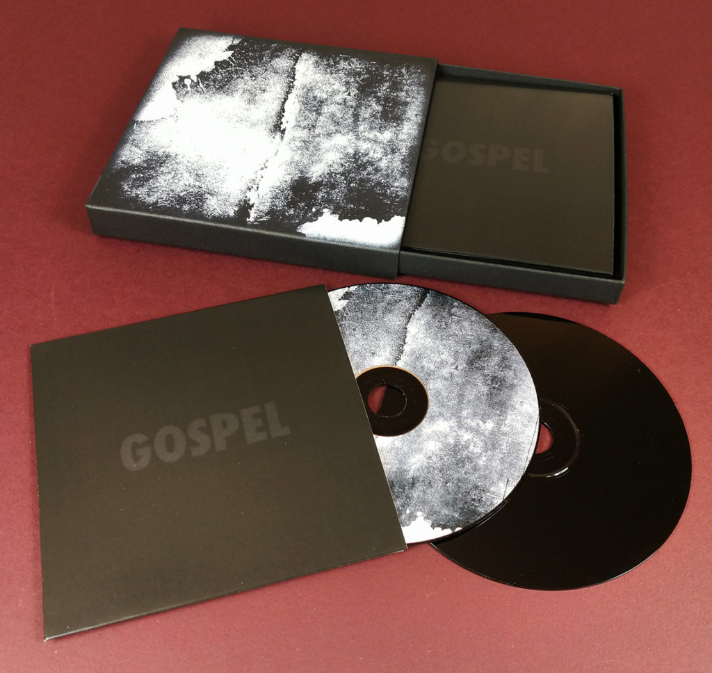Black matchbox-style CD set with black base discs and matching disc and cover abstract prints