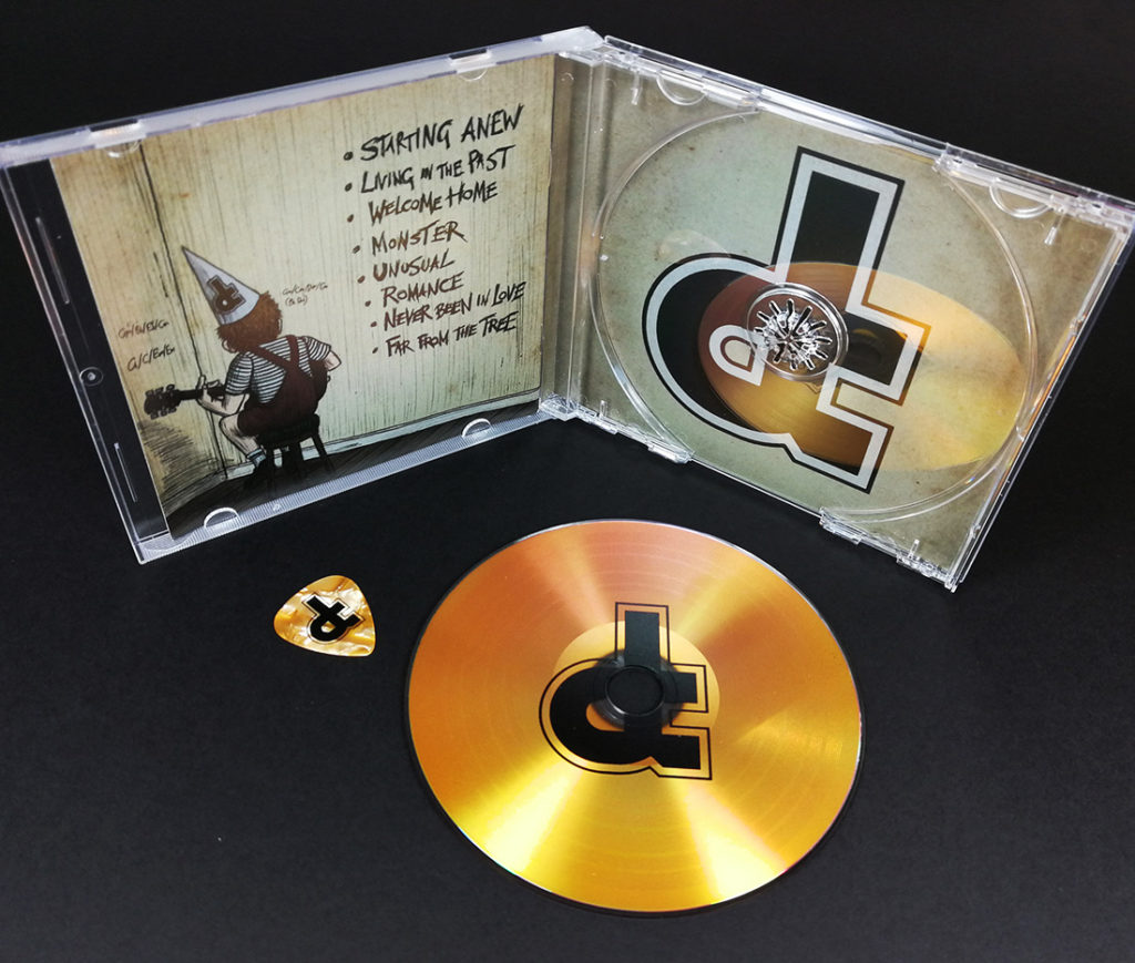 Gold vinyl CDs with gold guitar picks in CD jewel cases