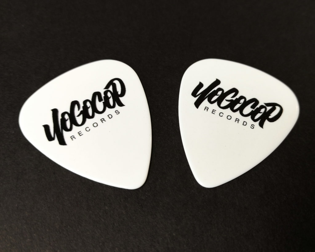 White guitar picks with a black print
