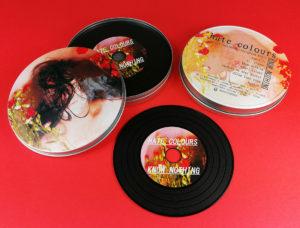Black vinyl CDs in printed metal tins