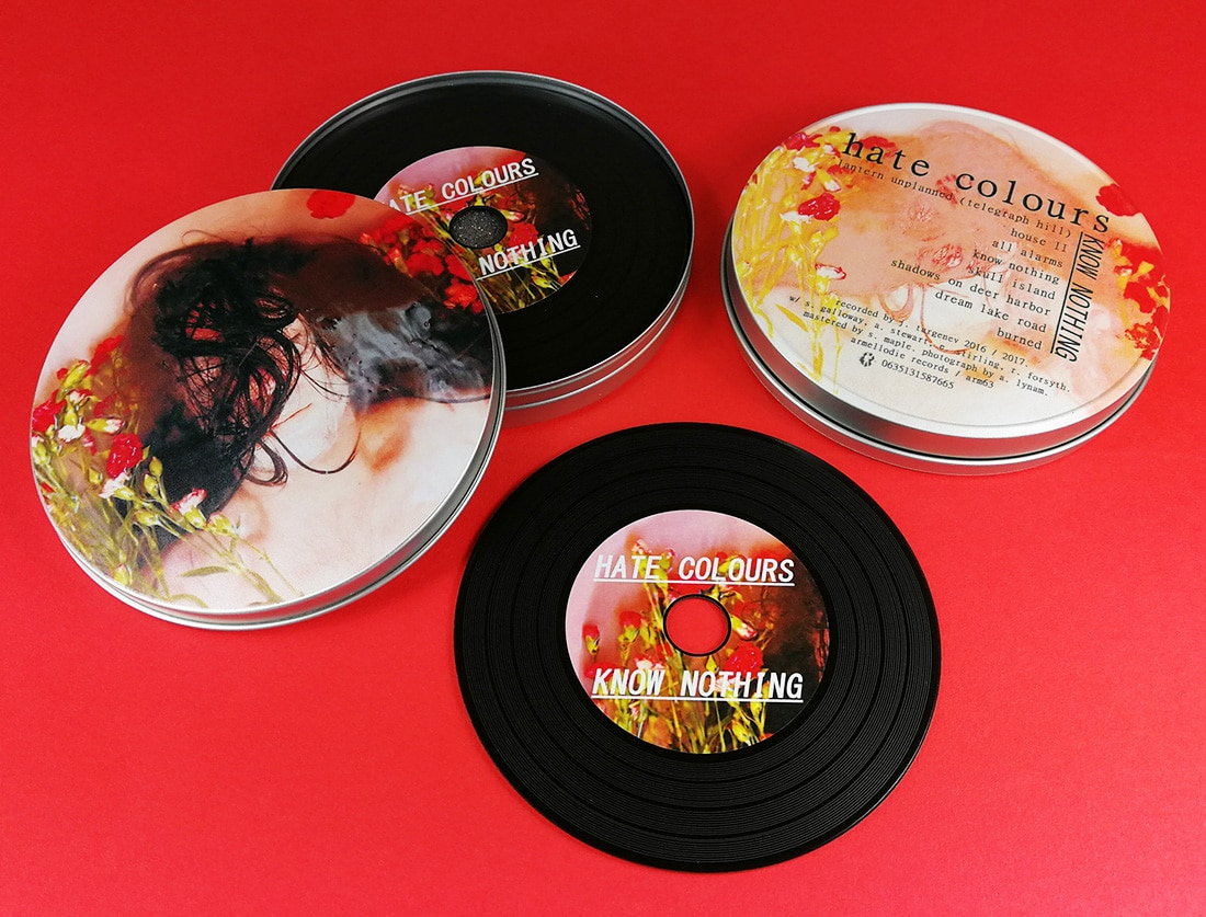 Black vinyl CDs in printed metal tins