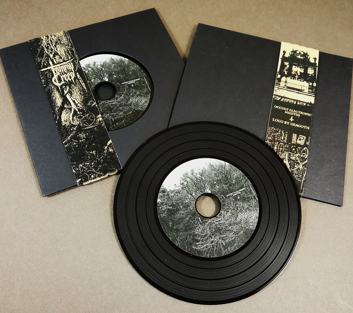 Black vinyl CDs in solid black record-style wallets with brown Manila obi-strips