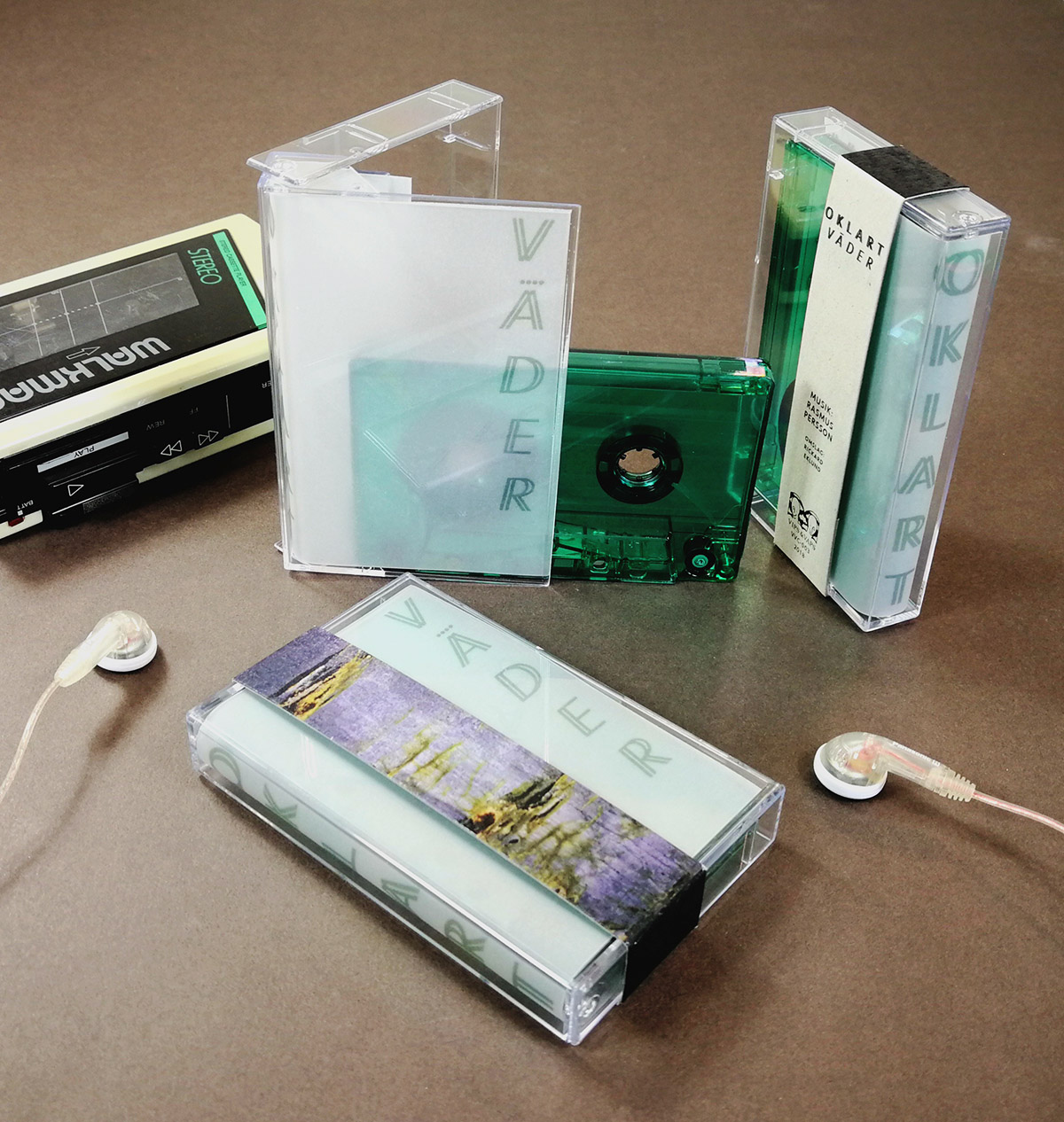 Dark green transparent unprinted cassettes in cases with tracing paper J-cards and Obi strips