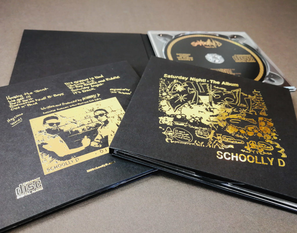 Solid black card CD digipaks with metallic gold foil printing and UV-LED printed gold discs