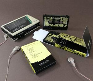 Black cassette tapes in printed Maltese cross folding card boxes