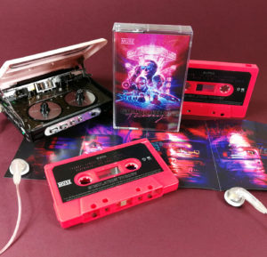 Neon pink cassettes with stickers and J-cards with three additional fold-out panels