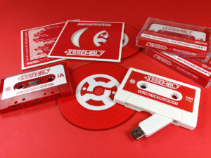 Red vinyl CDs in record-style wallets, red cassette tapes and white USB cassettes