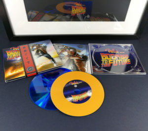 Custom vinyl CDs with orange vinyl rings on a blue base disc for a 'Back to the Future' style release