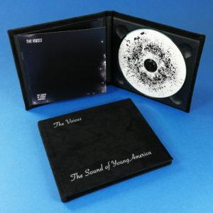 Black velvet hardback digipaks with white cover printing and booklets glued to the inner left panel