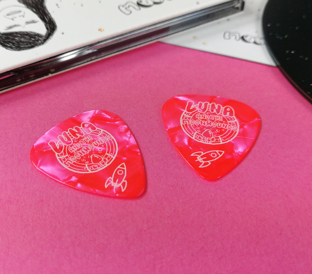Pink guitar picks with a single colour cream print for Luna and the Moonhounds