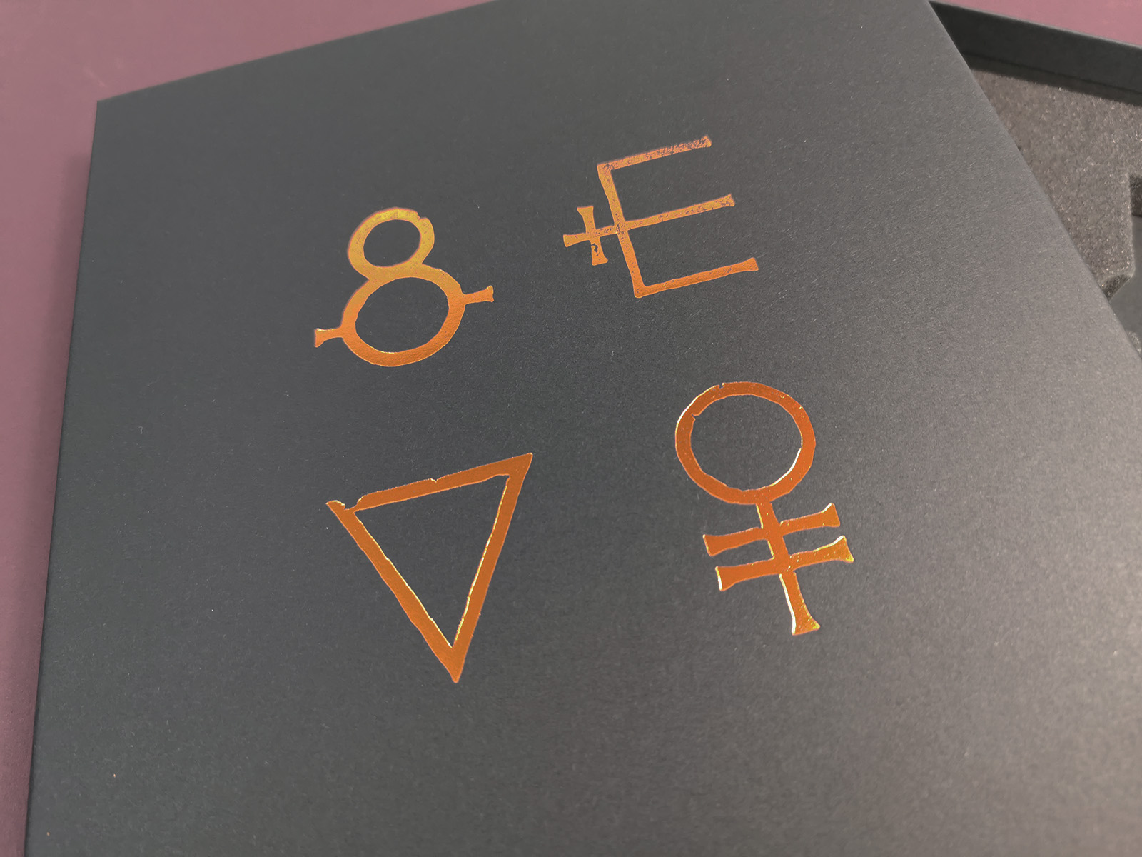 Close-up of copper metallic foil printing on a black A4 quad cassette tape presentation box