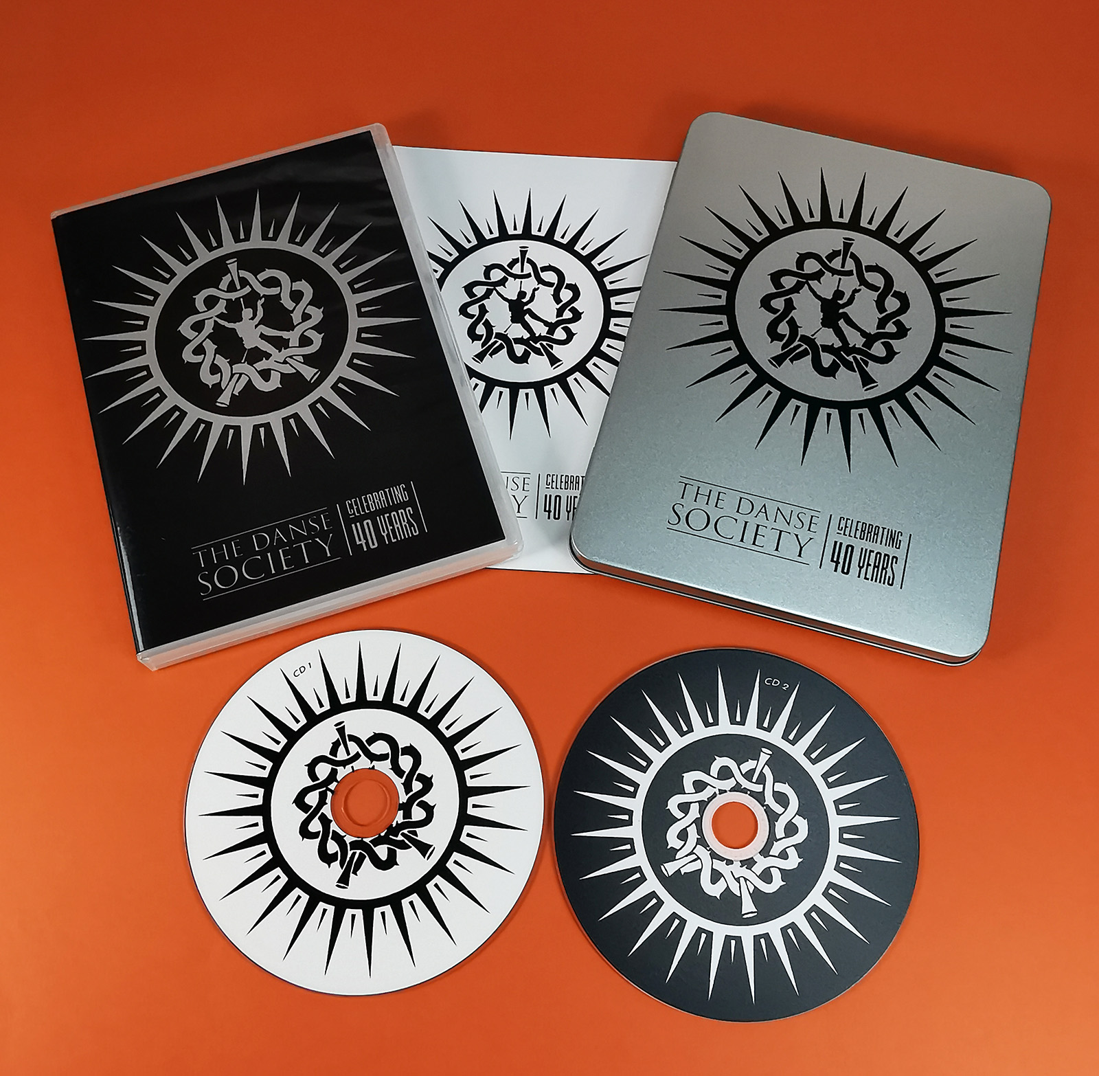 Metal DVD tins with a black on-body print and two CDs inside for The Danse Society