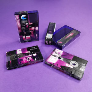 Silver glitter cassettes with a custom reveal on-body print, packed in purple back cases with obi strips